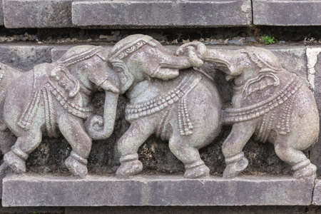 Belur, Karnataka, India - November 2, 2013: Chennakeshava Temple building. Stone plinth of three fighting elephants. Banque d'images - 120271086
