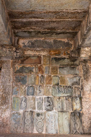 Belur, Karnataka, India - November 2, 2013: Chennakeshava Temple building. Wall under mandapam with multiple stone sculptures of intertwined snakes, symbol of Tamas, the destructive tendency, associated with Lord Shiva.