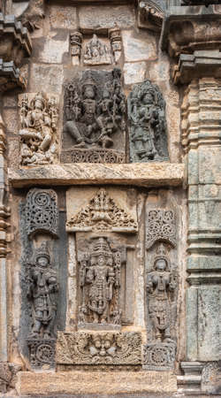 Belur, Karnataka, India - November 2, 2013: Chennakeshava Templ. Large Brown wall stone side panel sculpture of the three main gods each surrouned by their wives and consorts.