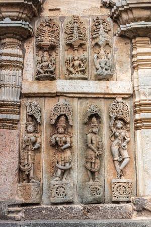 Belur, Karnataka, India - November 2, 2013: Chennakeshava Temple. Large Brown wall stone side panel sculpture of, top row, Vishnu and his two wives, bottom row, Shilabalikas, dancing girls.