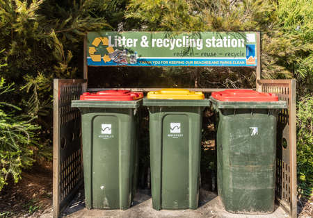 Sydney, Australia - February 11, 2019: Three green trash bins at the Liter and Recycling station on Tamarama Beach. Neatly set in an alcove backed by green vegetation.