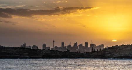 Sydney, Australia - February 12, 2019: Sunset over city skyline seen from Tasman Sea. Shoreline rocky cliffs. Yellow brown sky, sun rays. 5 of 5.