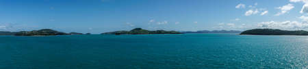 Whitsunday Island, Australia - February 16, 2019: Wide panorama shot of Whitsunday Island group with Hamilton Island to the left and Whitsunday in center. Azur sea and blue sky.