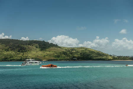 Hamilton Island, Australia - February 16, 2019: Jetski and two boats just outside the marina. Green hill in the back under blue sky with some white clouds.