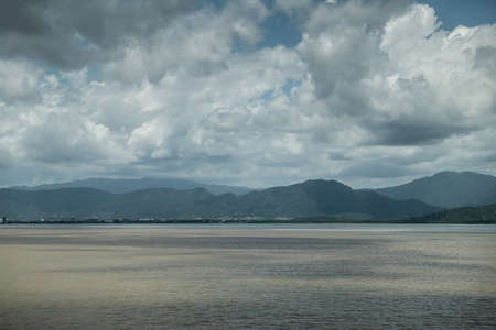 Cairns, Australia - February 17, 2019: Shallow and calm Coral Sea water in front of the town, white of buildings. Horizon of mountains north of the city part of Kuranda National Park under blue sky with white cloudscape. Stock Photo