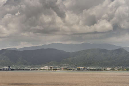 Cairns, Australia - February 17, 2019: Coral Sea water in front of the town, skyline of buildings. Horizon of mountains north of the city part of Kuranda National Park under rainy sky with dark cloudscape.