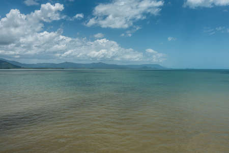 Cairns, Australia - February 17, 2019: Shallow and calm Coral Sea water in front of the town. Horizon of mountains north of the city part of Kuranda National Park under blue sky with white cloudscape.