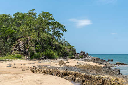 Cairns, Australia - February 18, 2019: Closeup of North end of warm beige tropical beach and rocks of Palm Cove with azure Coral Sea water under blue sky.