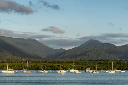 Cairns, Australia - February 18, 2019: Evening shot at sunset. Anchored white small sailing boats on Chinaman Creek under heavy cloudscape. Backdrop is rainforest hills.