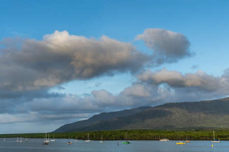 Cairns, Australia - February 18, 2019: Evening shot at sunset. Anchored small sailing boats on Chinaman Creek under heavy cloudscape. Backdrop is rainforest hills.