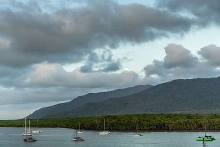Cairns, Australia - February 18, 2019: Evening shot at sunset. Anchored small sailing boats on Chinaman Creek under heavy cloudscape. Backdrop is rainforested hills.