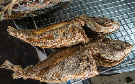 Sihanoukville, Cambodia - March 15, 2019: Phsar Leu Market. Closeup of two freshly grilled and browned fishes, lying on a metal grid.