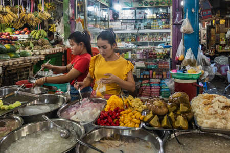 Sihanoukville, Cambodia - March 15, 2019: Phsar Leu Market. Two young women prepare and serve fast food, fruits, pickles and more out of basins and pot. Other stores in back. 新聞圖片