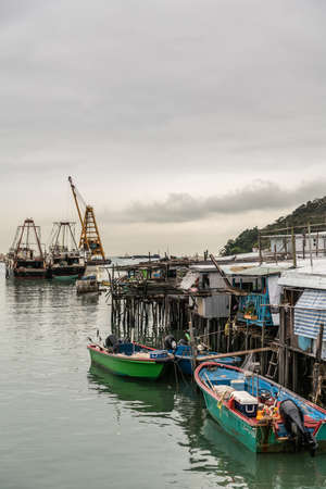 Hong Kong, China - March 7, 2019: Tai O Fishing village. Modern larger fishing vessels docked in port and small sloops under cloudscape with yellowish horizon over sea. Editorial