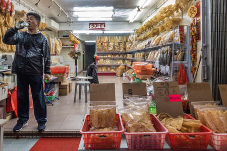Hong Kong, China - March 7, 2019: Tai O Fishing village. Shop owner is black clothes drinks water while guarding his large dried seafood store, displying all yellowish merchandise on shelfs and in red baskets.