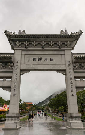 Hong Kong, China - March 7, 2019: Lantau Island, Po Lin Buddhis Monastery. Central segement of Monumental gray entrance gate to the domain. Rainy conditions, green hills and gray cloudy sky.