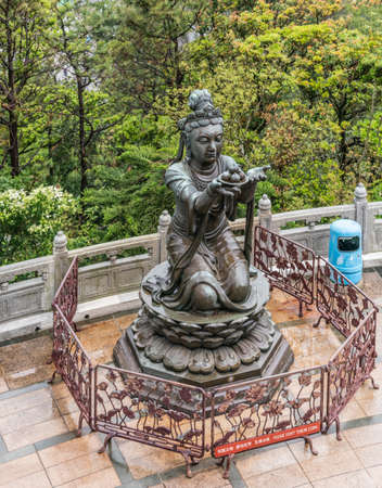 Hong Kong, China - March 7, 2019: Lantau Island. One of the Six Devas offers fruit to Tian Tan Buddha. Bronze statue seen from higher up with green foliage in back.