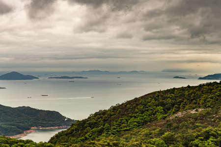 Hong Kong, China - March 7, 2019: Lantau Island. Pearl River estuary and South China Sea seen from Tian Tan Buddha platform. Green forested hill up front. Islands, boats, shorelines under heavy rainy cloudscape.