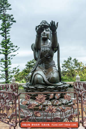 Hong Kong, China - March 7, 2019: Lantau Island. One of the Six Devas offers fruit to Tian Tan Buddha. Bronze statue seen from front with green foliage and ligh blue sky in back.
