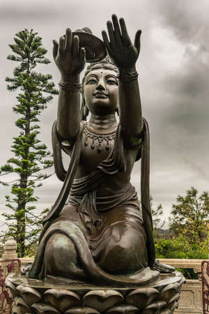 Hong Kong, China - March 7, 2019: Lantau Island. Closeup, One of the Six Devas offers fruit to Tian Tan Buddha. Bronze statue seen from front with green foliage and rainy sky in back.