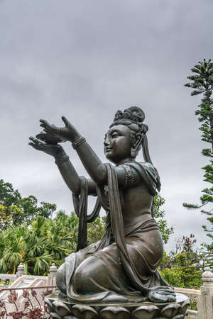 Hong Kong, China - March 7, 2019: Lantau Island. Side Closeup, One of the Six Devas offers fruit to Tian Tan Buddha. Bronze statue seen from front with green foliage and rainy sky in back. Stock Photo
