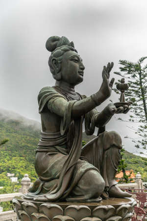 Hong Kong, China - March 7, 2019: Lantau Island. Side Closeup, One of the Six Devas offers lamp to Tian Tan Buddha. Bronze statue seen from front with green foliage and rainy sky in back.