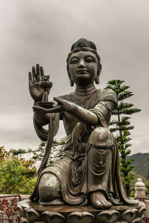 Hong Kong, China - March 7, 2019: Lantau Island. Closeup, One of the Six Devas offers lamp to Tian Tan Buddha. Bronze statue seen from front with green foliage and rainy sky in back.