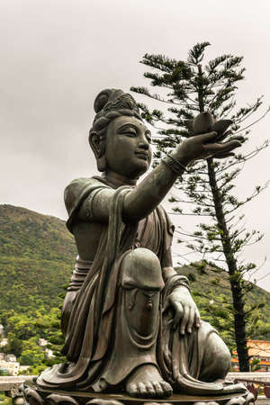 Hong Kong, China - March 7, 2019: Lantau Island. Closeup, One of the Six Devas offers flower to Tian Tan Buddha. Bronze statue seen from front with green foliage and rainy sky in back. Stock Photo
