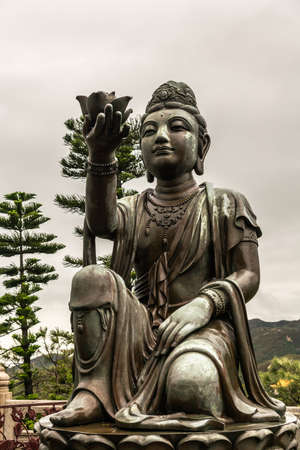 Hong Kong, China - March 7, 2019: Lantau Island. Front Closeup, One of the Six Devas offers flower to Tian Tan Buddha. Bronze statue seen from front with green foliage and rainy sky in back. Stock Photo