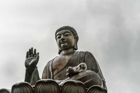 Hong Kong, China - March 7, 2019: Lantau Island. Frontal Closeup of Tian Tan Buddha statue from down under showing face, chest and lotus leaf under silver sky. Stock Photo