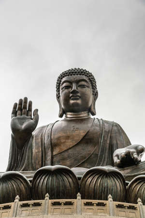 Hong Kong, China - March 7, 2019: Lantau Island. Frontal Facial view of Tian Tan Buddha statue from down under showing face, chest, lotus leaves and stone fence under silver sky.