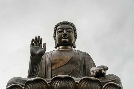 Hong Kong, China - March 7, 2019: Lantau Island. Frontal Facial closeup of Tian Tan Buddha statue from down under showing face, chest, and lotus leaves under silver sky. Stock Photo