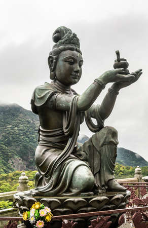 Hong Kong, China - March 7, 2019: Lantau Island. Closeup, One of the Six Devas offers ointment to Tian Tan Buddha. Bronze statue seen from front with green hill and rainy sky in back. Stock Photo