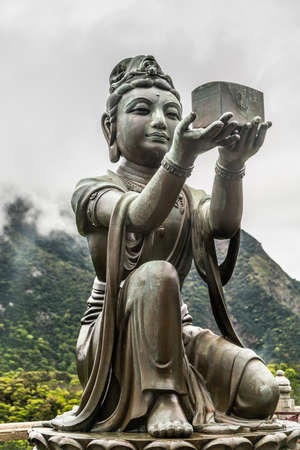 Hong Kong, China - March 7, 2019: Lantau Island. Closeup, One of the Six Devas offers music box to Tian Tan Buddha. Bronze statue seen from front with green hill and rainy sky in back. Stock Photo