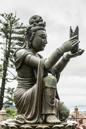 Hong Kong, China - March 7, 2019: Lantau Island. Side Closeup, One of the Six Devas offers incense sticks to Tian Tan Buddha. Bronze statue seen from front with green hill and rainy sky in back.