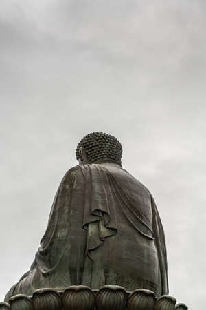 Hong Kong, China - March 7, 2019: Lantau Island. Tian Tan Buddha shows his back, statue from down under, back of body and lotus leaves under silver sky. Stock Photo