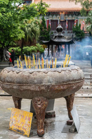 Hong Kong, China - March 7, 2019: Lantau Island. Po Lin Buddhist Monastery. Large brown stone, metal receptacle wherein incense sticks burn in front of red Hall and green foliage. Stock Photo