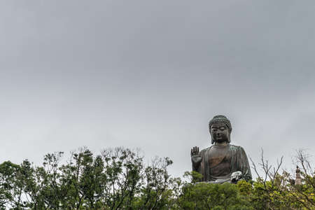 Hong Kong, China - March 7, 2019: Lantau Island. Frontal view, Tian Tan Buddha peeps over trees, statue from down under farther away under rain promising sky.