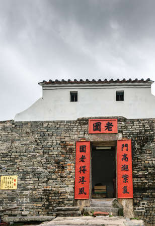 Hong Kong, China - March 8, 2019: New Territory. Watchtower and entrance to Tang Family Compound. Door with red banner framing, gray and brown brick wall with white lookout structure on top.