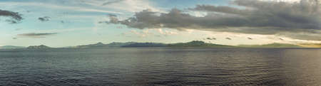 East Nusa Tenggara Island, Indonesia - February 24, 2019: Early morning at sunrise. Panorama shot of Southside coast off Sessok in Savu Sea under cloudscape with azure, blue and yellow patches. Dark sea and green hills