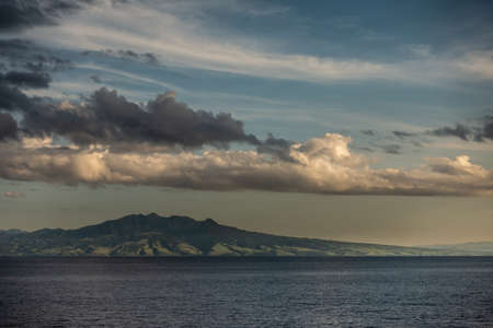 East Nusa Tenggara Island, Indonesia - February 24, 2019: Early morning at sunrise. Southside coast off Sessok in Savu Sea under cloudscape with yellow and darker patches. Dark sea and green hills