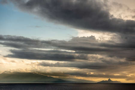 East Nusa Tenggara Island, Indonesia - February 24, 2019: Early morning at sunrise. Southside coast off Sessok in Savu Sea under cloudscape with yellow and darker patches. Dark sea, small Mules island silhouettes. Stockfoto