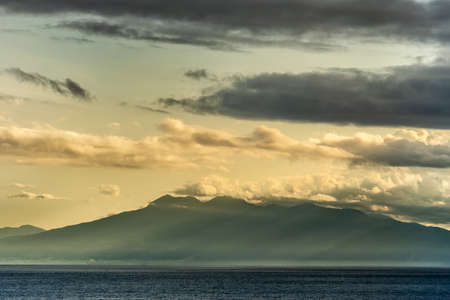 East Nusa Tenggara Island, Indonesia - February 24, 2019: Early morning at sunrise. Southside coast off Sessok in Savu Sea under cloudscape with yellow and darker patches. Dark sea, hill silhouettes.