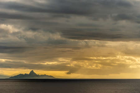 East Nusa Tenggara Island, Indonesia - February 24, 2019: Early morning at sunrise. Southside coast off Sessok in Savu Sea under cloudscape with yellow and darker patches. Dark sea, hill silhouette of Mules Island. Stockfoto