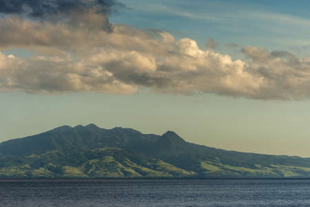 East Nusa Tenggara Island, Indonesia - February 24, 2019: Early morning at sunrise. Southside coast off Sessok in Savu Sea under cloudscape with azure, white and darker patches. Dark sea and green hills