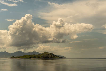 Rinca Island, Indonesia - February 24, 2019: Islet on Westside coast in Savu Sea under cloudscape with white and darker patches. Green hills and flat sea. Stockfoto
