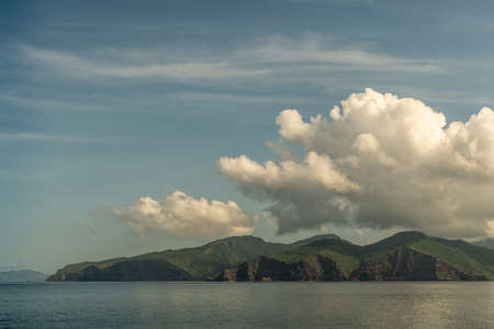 Rinca Island, Indonesia - February 24, 2019: Early morning. Southside coast in Savu Sea under cloudscape with white and darker patches.Green hills and cliffs.