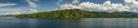 Komodo Island, Indonesia - February 24, 2019: Panorama shot of Komodo National Park in blue sea. Green forested hills in back under blue sky with white clouds. Strip of sandy beach with pier.