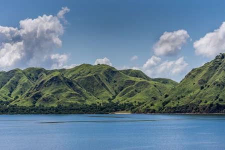 Komodo Island, Indonesia - February 24, 2019: Green mountain range descending on sand beach under blue sky with cloudscape, part of Komodo National Park. 版權商用圖片
