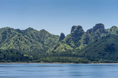 Komodo Island, Indonesia - February 24, 2019: Green mountain range descending on sand beach under blue sky, part of Komodo National Park.